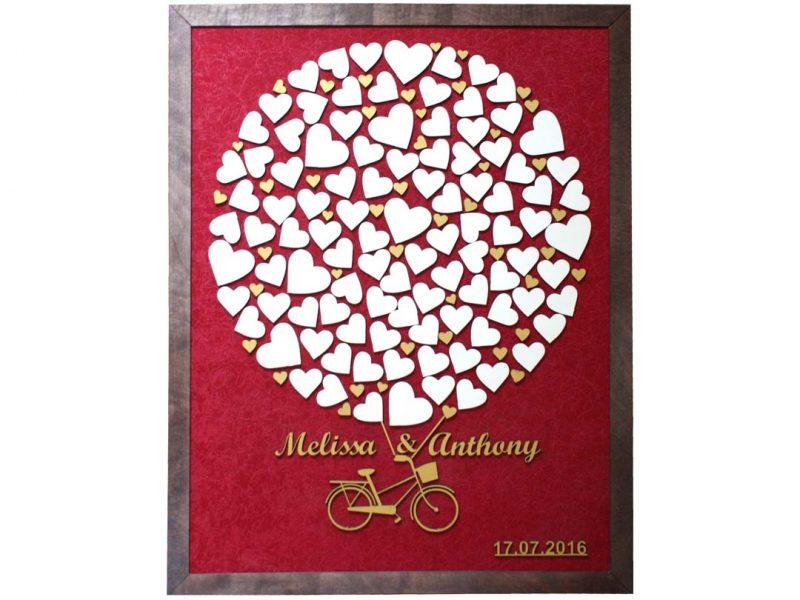 Cuadro para firmas y mensajes de boda modelo Sara, con lienzo en tela vinotinto y marco nogal. Detalles decorativos en dorado.